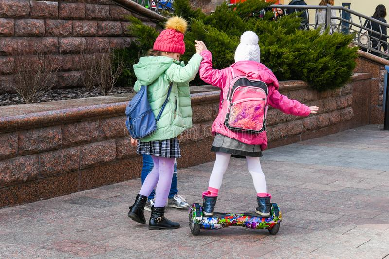 Child on hover board. Kids riding scooter in summer park. Balance board for children. Electric self balancing scooter on city stock image