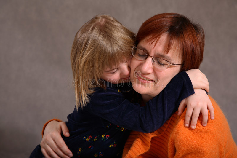 Child hugs mother. Portrait of a mother and child as girl hugs mother royalty free stock photo