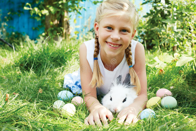 Child hunted on Easter egg in blooming spring garden. Child with white bunny searching for colorful eggs on meadow stock photo