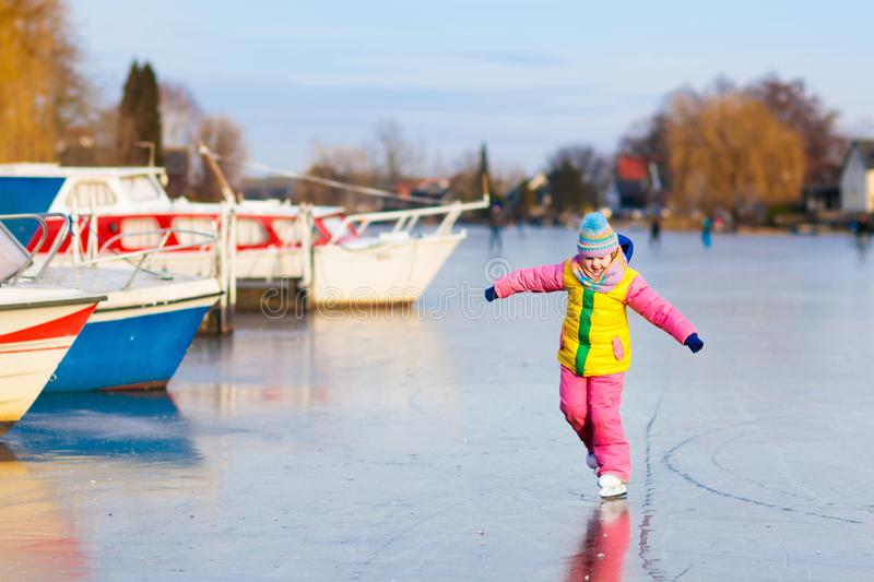 Child ice skating on frozen mill canal in Holland. stock photos