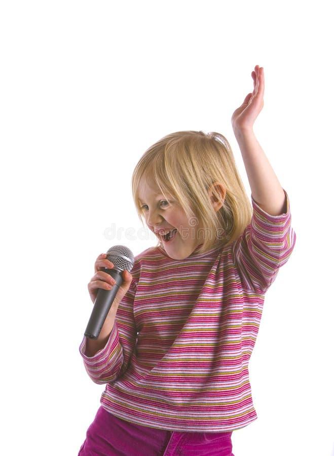 Child Idol. A child wannabe pop idol with microphone stock image
