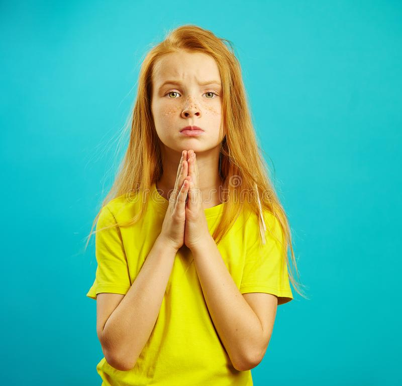 Child with imploring glance, she folded her hands at the breast in sign of supplication or request, expressed apology. And willingness to purchase toys stock image