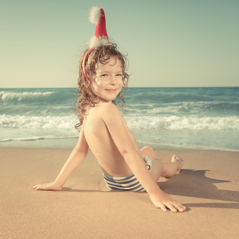 Free Child In Santa Hat At The Beach Stock Photography - 34325032