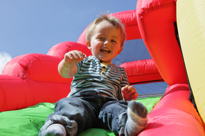Child on inflatable bouncy castle slide. 2 year old boy jumping down the slide on an inflatable bouncy castle stock photography