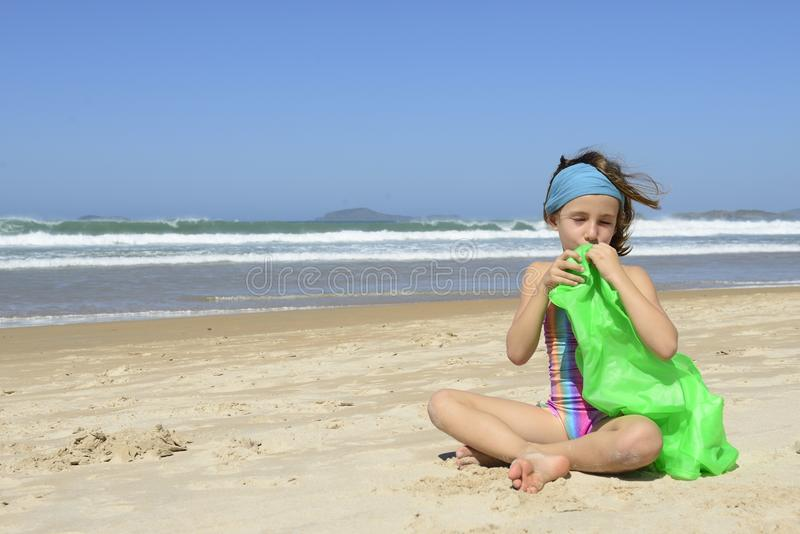Child inflating inflatable swim ring on the beach. Summer vacation: Child inflating inflatable swim ring on the beach stock photos