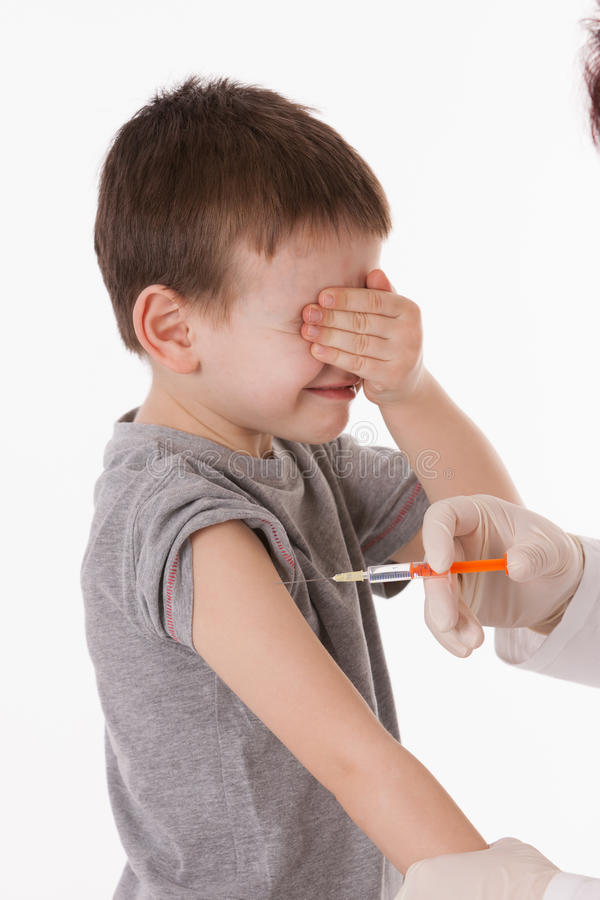 Child with injection. Doctor giving a child injection in arm on isolated image royalty free stock photography
