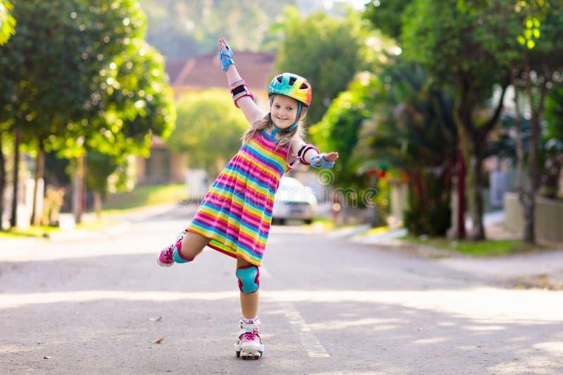 Child on inline skates. Kids skate roller blades. Child on inline skates in park. Kids learn to skate roller blades. Little girl skating on sunny summer day royalty free stock image