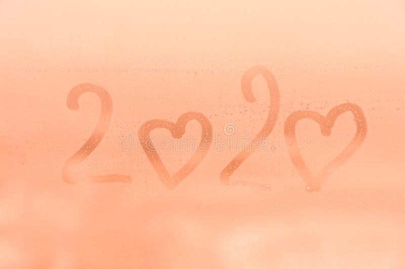 The child inscription 2020 with the hearts symbols instead zeros on the orange or pink evening or morning window glass royalty free stock image