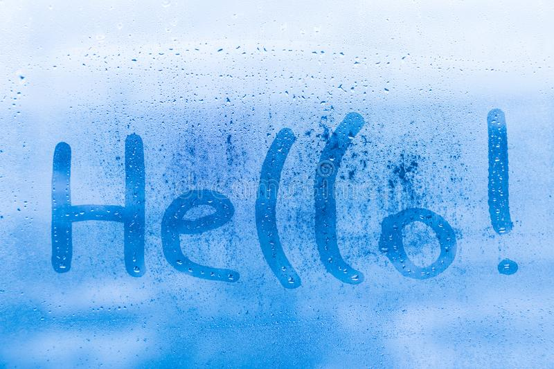 The child inscription hello on the blue evening or morning window glass stock photos
