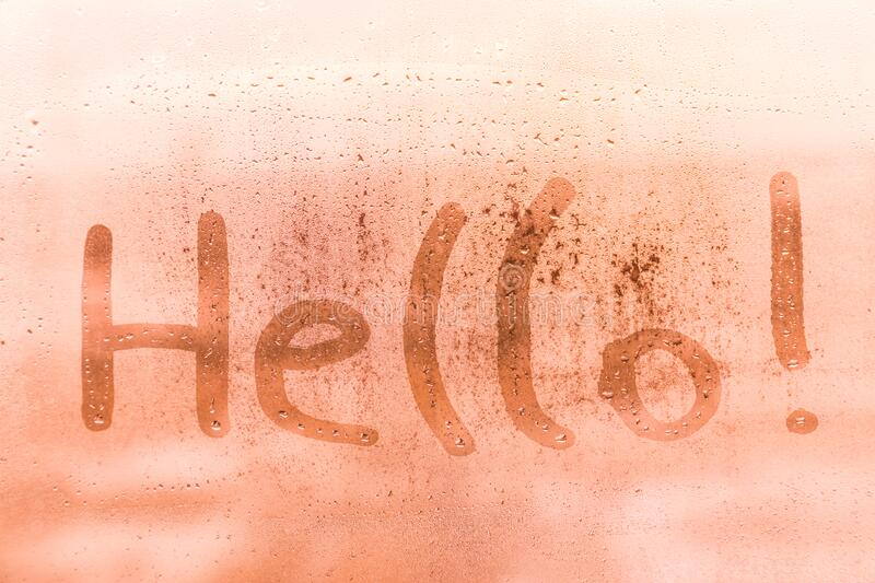 The child inscription hello on the orange or pink evening or morning window glass royalty free stock photography