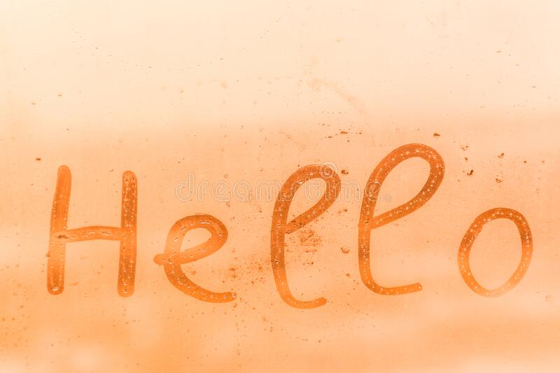 The child inscription hello on the orange or pink evening or morning window glass stock image