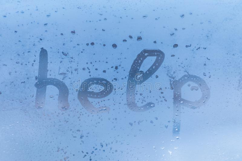 The child inscription help on the blue evening or morning window glass stock photography