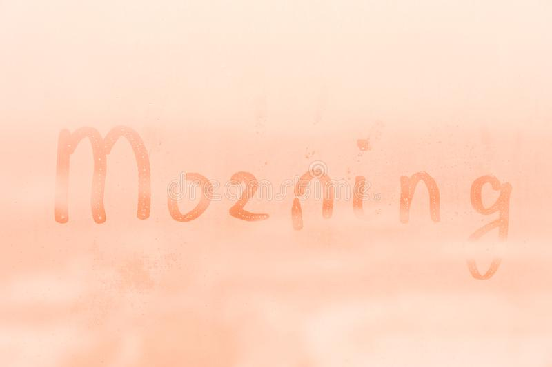 The child inscription morning on the orange and pink evening or morning window glass royalty free stock image