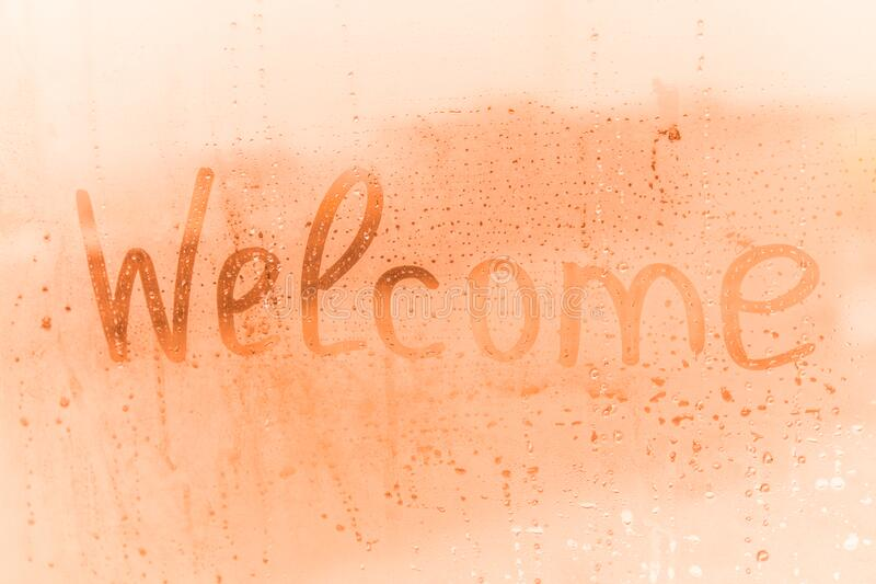 The child inscription welcome on the orange or pink evening or morning window glass royalty free stock image