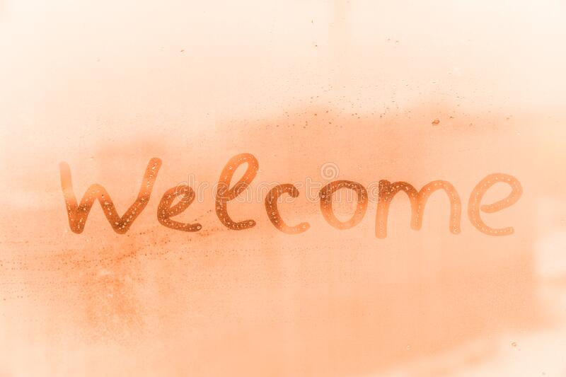 The child inscription welcome on the orange or pink evening or morning window glass stock photo