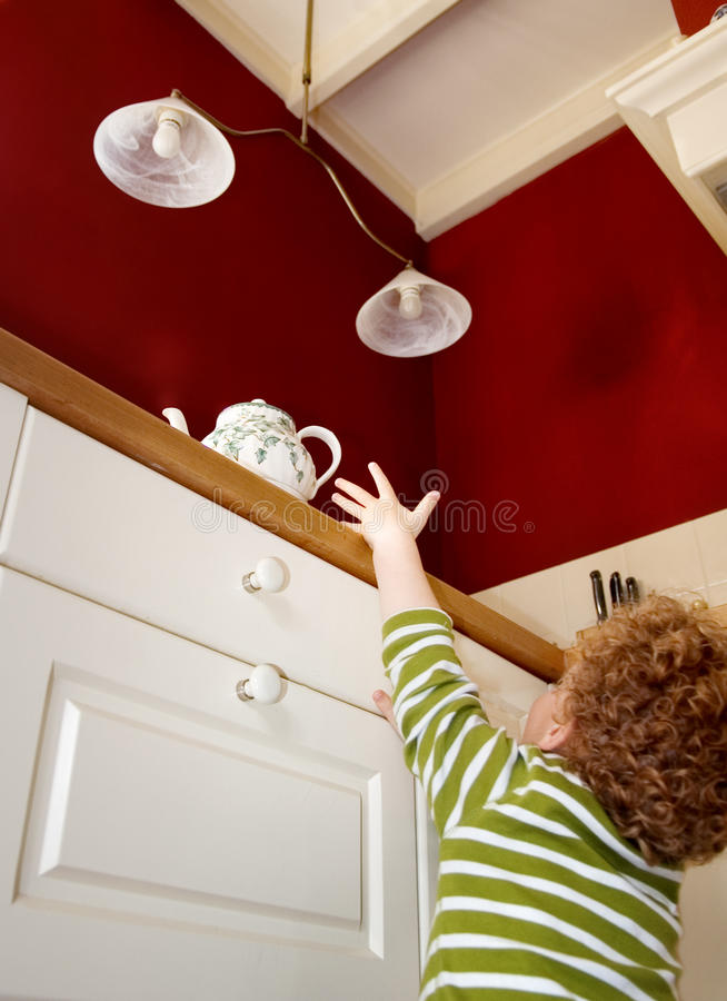 Child insecurity at Home. Small child reaching for a dangerous hot teapot on the kitchen counter top, photo taken from below stock photography