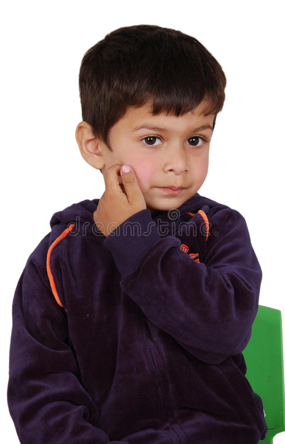 Child itching his face. A lovely child itching his face with his nails and is lost in dreamy world royalty free stock image