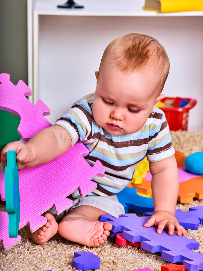 Child jigsaw develops children. Kid puzzle making baby. Little boy holding big pieces . Playing on floor in kindergarten royalty free stock image