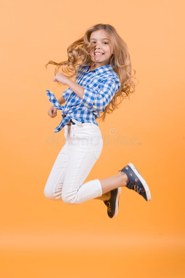 Child jump smiling on orange background. Child bounce with happy face royalty free stock photo