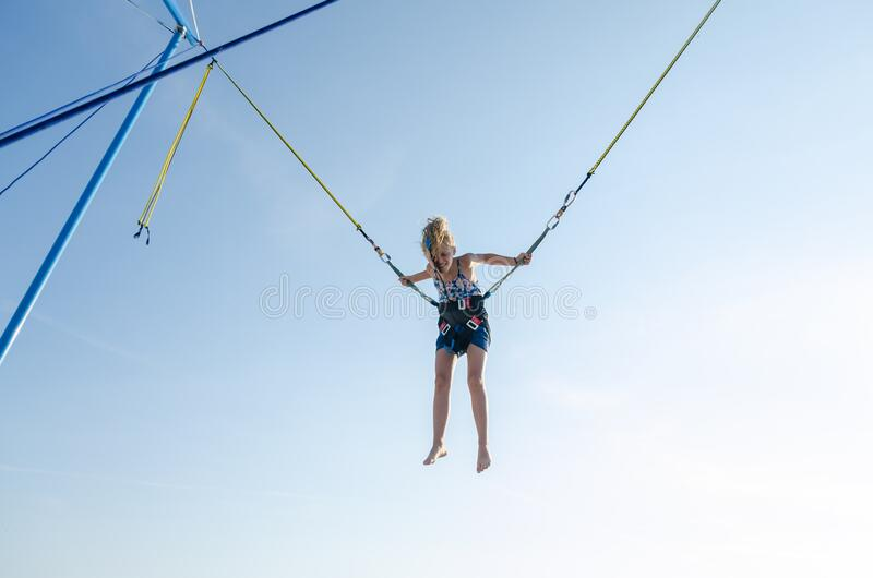 Child jumping in the jumping attraction. Active little young teen girl jumping in trampoline high into the blue sky safed with  elastic safety belt royalty free stock photo