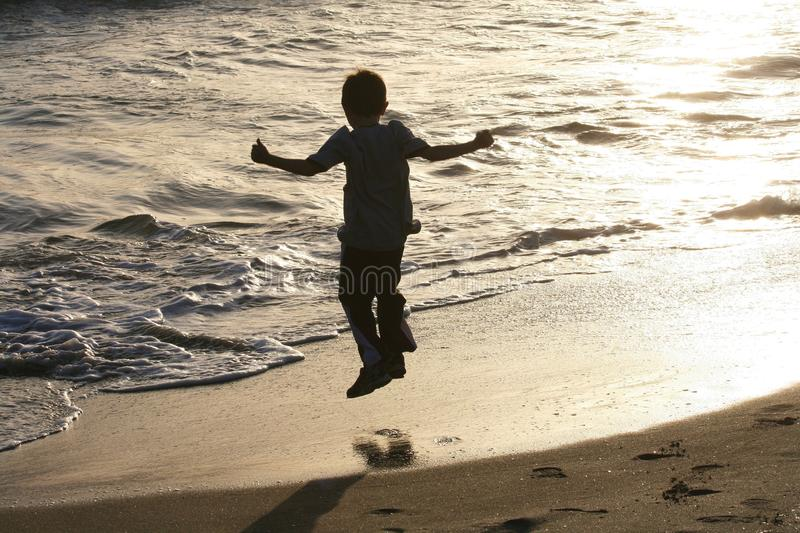 Child jumping on beach royalty free stock images