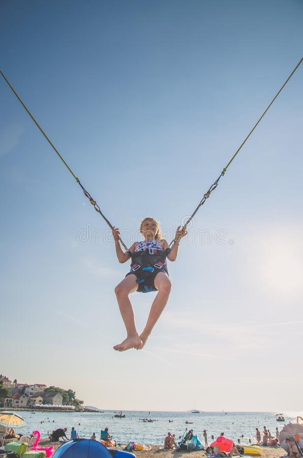 Child jumping in the jumping attraction in the seaside beach. Active little young teen girl jumping in trampoline high into the blue sky safed with  elastic royalty free stock photography