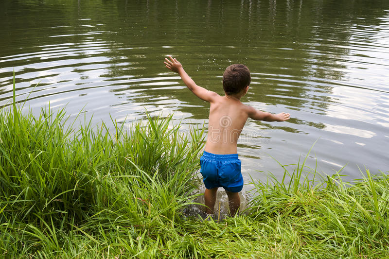 Child jumping into lake or pond stock photos