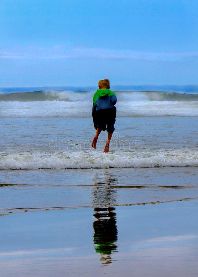 Child Jumping Waves at Beach royalty free stock photos