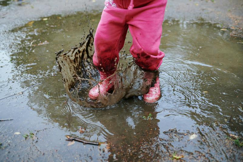 Child jumps in a dirty puddle royalty free stock image