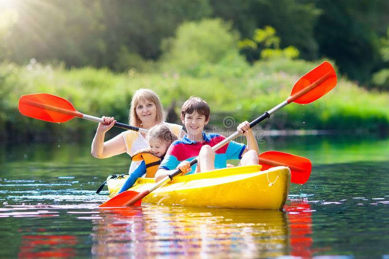 Child on kayak. Kids on canoe. Summer camping. Child with paddle on kayak. Summer camp for kids. Kayaking and canoeing with family. Children on canoe. Little stock photography
