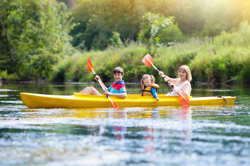 Child on kayak. Kids on canoe. Summer camping. Child with paddle on kayak. Summer camp for kids. Kayaking and canoeing with family. Children on canoe. Family on stock image