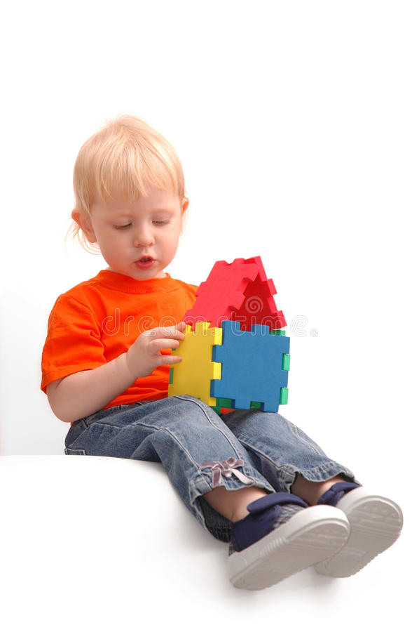 Child keeps house from pazzls. On white background stock photography