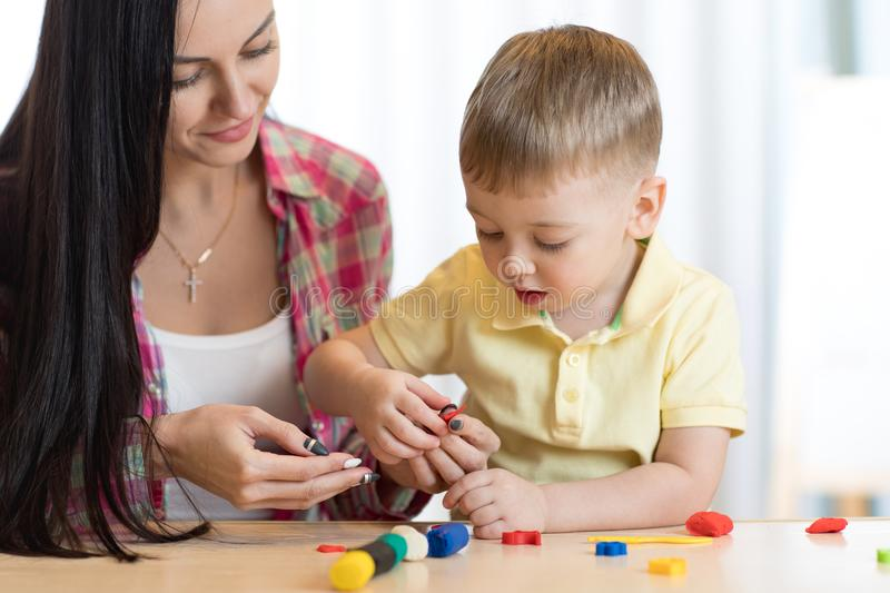 Child kid boy and mother play colorful clay toy at nursery or kindergarten royalty free stock images