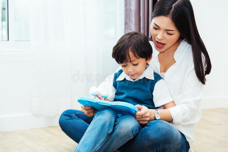 Child kid boy son kindergarten and beautiful mother teaching drawing together royalty free stock image