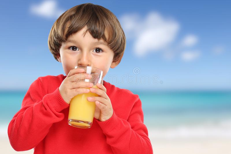 Child kid drinking orange juice beach summer sea healthy eating. Vacation royalty free stock images