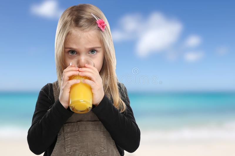 Child kid drinking orange juice beach summer sea healthy eating. Vacation stock images