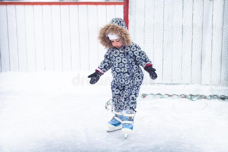 Child kid enjoy learning ice skating on skating rink overcome difficulties in a snowing park during winter holidays. Child kid enjoy learning ice skating on stock photos