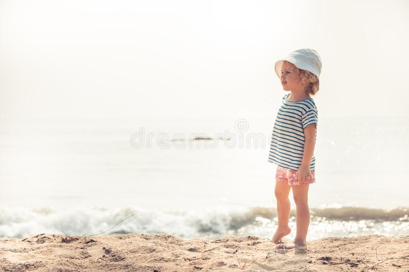 Child kid girl on beach looking into the distance searching for something with bright sunlight concept happy childhood lifestyle royalty free stock photography