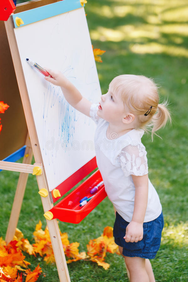 Child kid girl standing outside in summer autumn park drawing on easel with markers looking away playing studying. White Caucasian toddler child kid girl stock photo