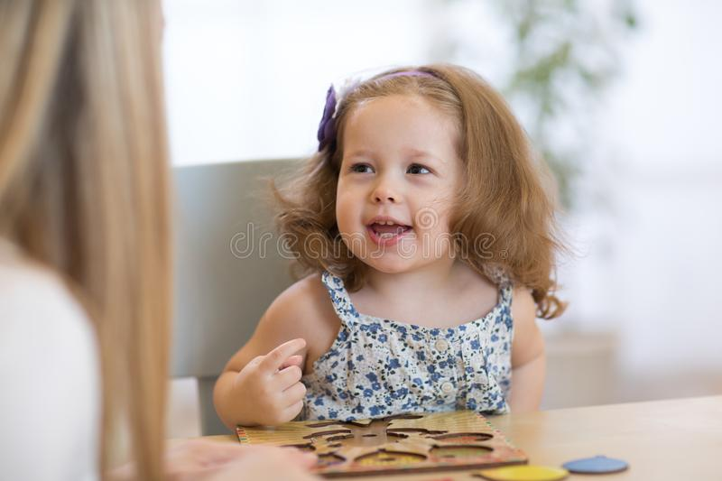 Child kid playing with puzzle shapes on table in children room in nursery or preschool. stock images