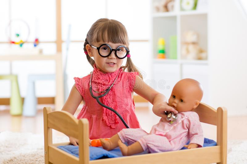 Child in kindergarten. Kid in nursery school. Little girl preschooler playing doctor with doll. stock images