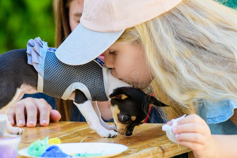 Child kisses a dog, love for pets. girl with long hair and a cap. gift baby dog stock photos