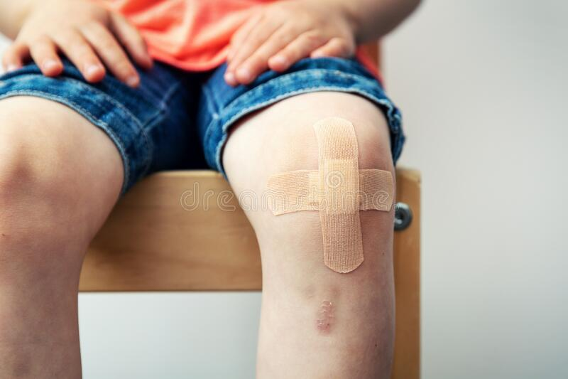 Child knee with adhesive bandage and bruise royalty free stock image