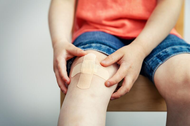 Child knee with adhesive medical plaster strip bandage royalty free stock images