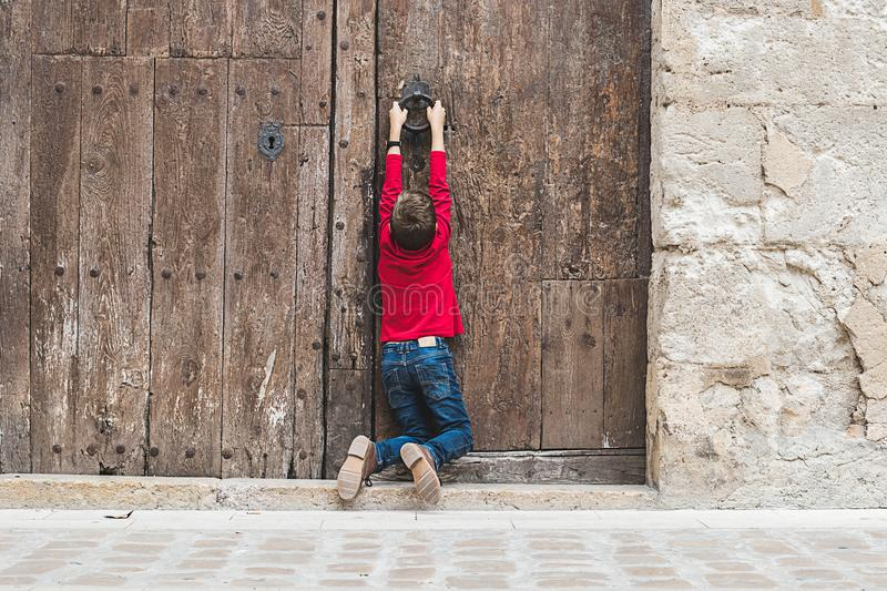 Child knocking on an old door. In the street stock images
