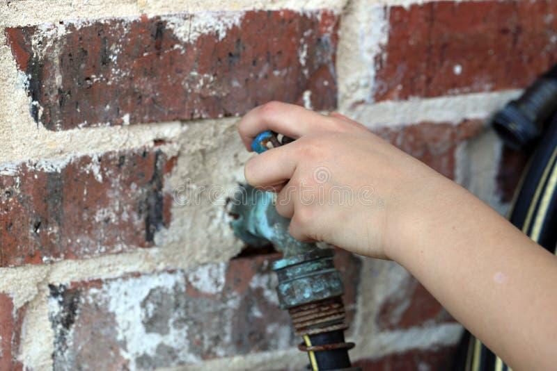 Child& x27; la mano di s gira il rubinetto di acqua del tubo flessibile fotografie stock libere da diritti