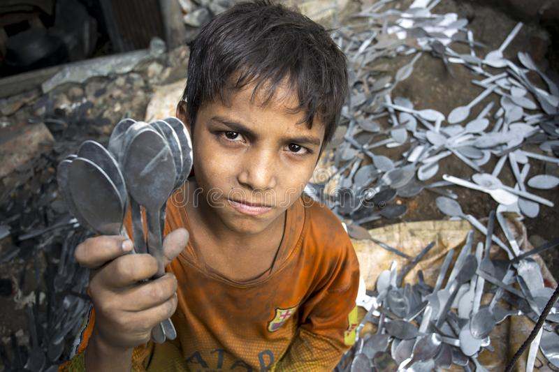 A child labor showing unmaking steel spoon. royalty free stock photos