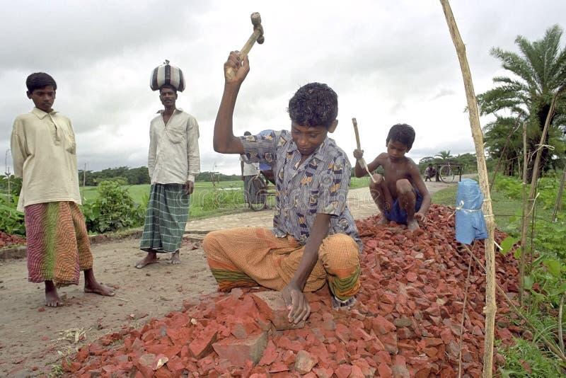 Child Labour stone breakers in road construction. Bangladesh, village and island Kalaiya in the Gulf of Bengal: portrait of Bengali boys, Bangladeshi children stock image