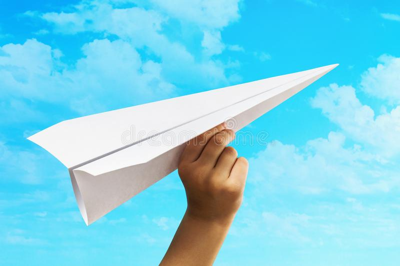 A child launches a paper plane into the sky. Concept on opening a new business and striving forward.  royalty free stock image