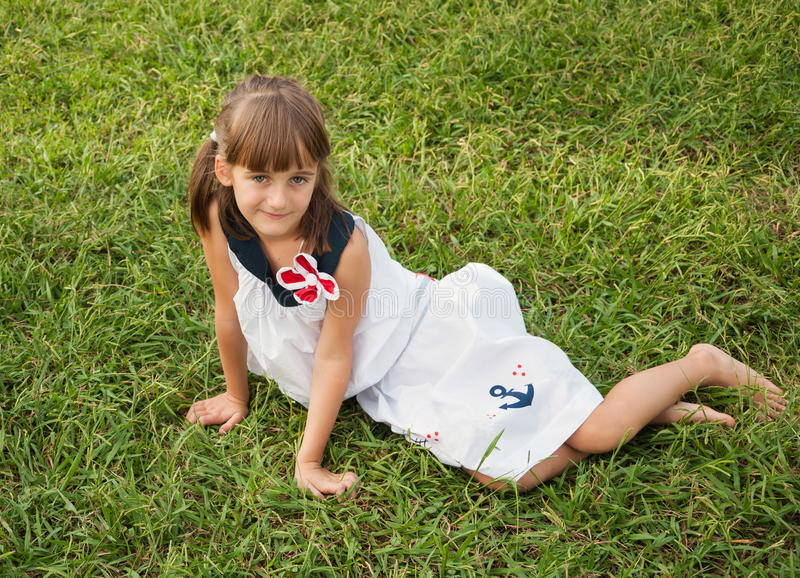 Child on the lawn. Beautiful girl with a flirty smile sitting on the lawn royalty free stock photo